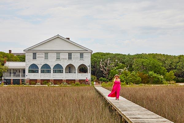 Woman walking on boardwalk over the marsh grass